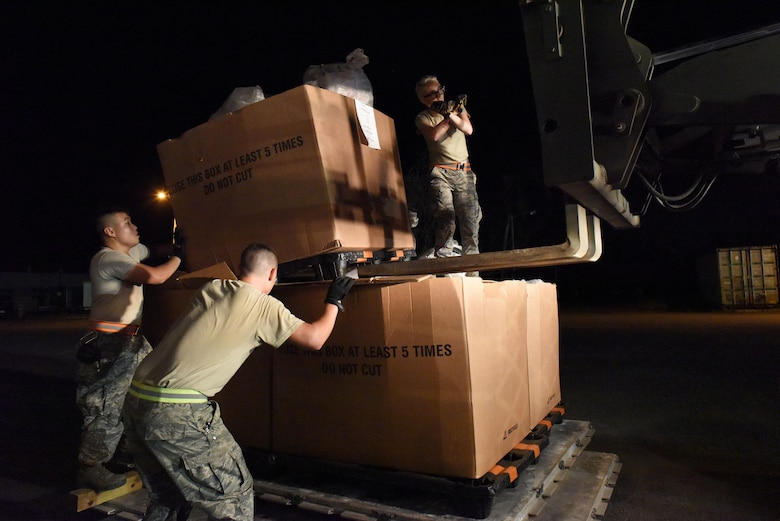 Aerial Port Airmen from Alaska Air National Guard's 176th Airlift Wing, Connecticut ANG's 103rd Airlift Wing and the Puerto Rico ANG's 156th Airlift Wing work together to load 18 pallets of mail on trucks for the U.S. Postal Service at Muniz Air National Guard Base, Puerto Rico, Oct. 20.The PRANG served as a staging area for 18 pallets of mail transported on a C-17 aircraft from the Tennessee ANG's 164th Airlift Wing. Power outages and a large influx of care packages and relief items from around the world, in support of the 3.4 million U.S. citizens, have quadrupled the average volume of mail destined to the Caribbean island still in recovery after Hurricane Maria. (U.S. Air National Guard photo by Staff Sgt. Angel Oquendo)