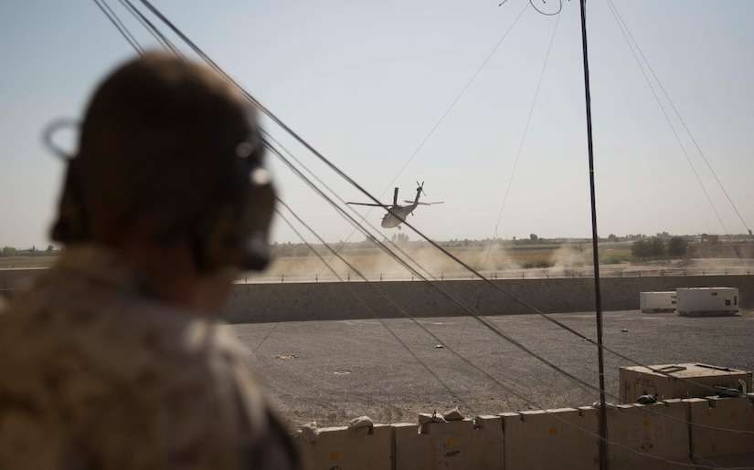 A U.S. Marine advisor and joint-terminal attack controller with Task Force Southwest listens in as a UH-60 Blackhawk departs after a key leader engagement at Bost Airfield, Afghanistan, Oct. 21, 2017. Task Force and Helmand-based Afghan National Defense and Security Force leadership collaborated to discuss courses of action for the second phase of Operation Maiwand Seven. Multiple elements of ANDSF, including the Afghan National Army 215th Corps, 505th Zone National Police and National Directorate of Security among others are working in conjunction to clear the Nad'Ali district of Taliban insurgents. (U.S. Marine Corps photo by Sgt. Justin T. Updegraff)