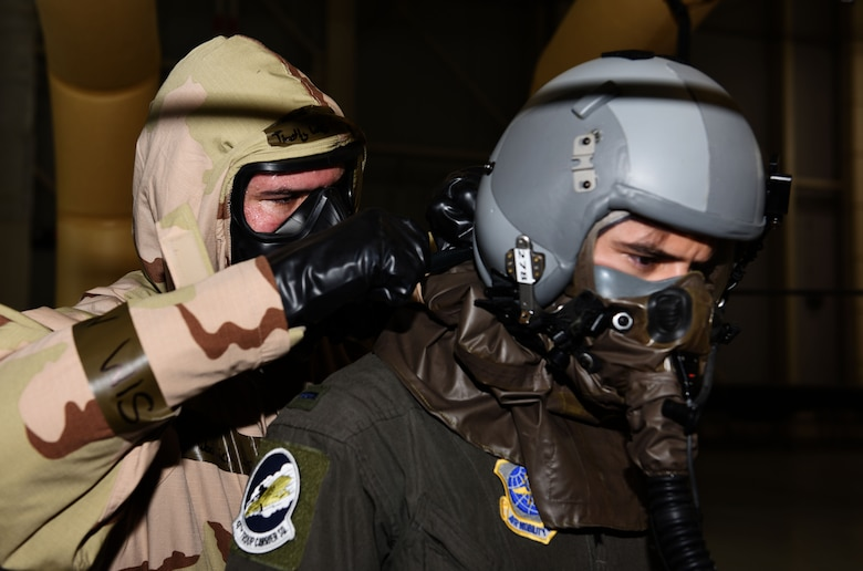 Staff Sgt. Timothy Wochnick, 317th Operations Support Squadron, aircrew flight equipment, assists 1st Lt. Garrett Iapicco, 40th Airlift Squadron, co-pilot through the decontamination line