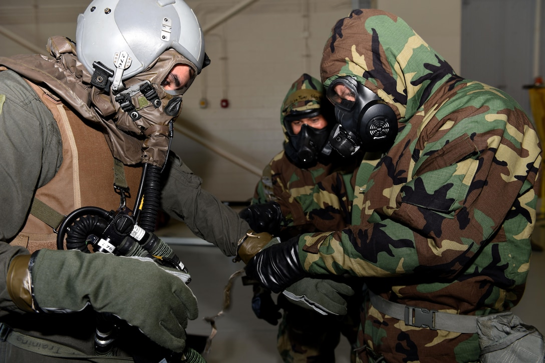 Two Airmen from the 317th Operations Support Squadron, aircrew flight equipment flight assist Senior Airman James Camera, 40th Airlift Squadron, loadmaster, through the decontamination line