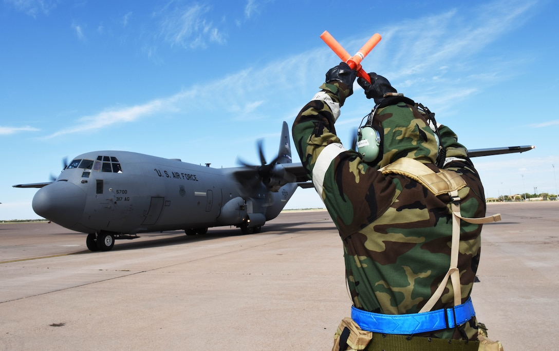 Staff Sgt. William Smith, 317th Aircraft Maintenance Squadron, flying crew chief, marshals a C-130J to a parking spot during the full spectrum readiness sortie