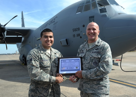 Senior Airman Julian Santiago, 19th Maintenance Squadron dedicated crew chief, receives the key to Little Rock's newest C-130J from Yakota AB, Japan