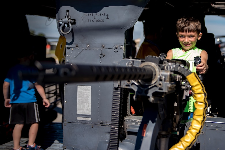 Neal Brooks, son of Staff Sgt. Neal Brooks, 23d Aerospace Medicine Squadron optometry technician, holds the handles of a .50-caliber machine gun, during the Thunder Over South Georgia Air Show, Oct. 28, 2017, at Moody Air Force Base, Ga. The machine gun is attached to an HH-60G Pave Hawk, used in the 23d Wing's rescue missions. (U.S. Air Force photo by Senior Airman Daniel Snider)