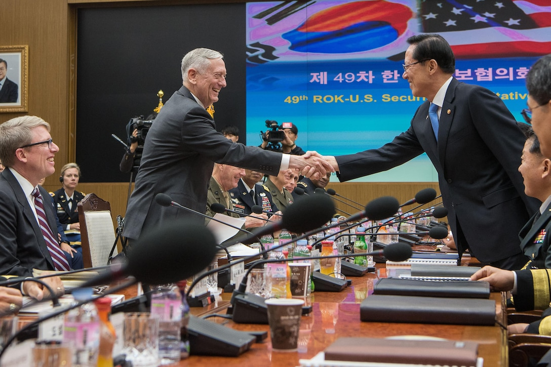 U.S. and South Korean defense leaders shake hands during a security meeting.