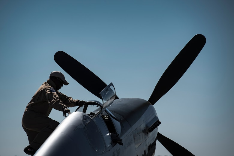 A performer climbs into a P-51 Mustang during the Thunder Over South Georgia Air Show, Oct. 29, 2017, at Moody Air Force Base, Ga. The open house is an opportunity for Moody to thank the local community for all its support, and exhibit air power and it included aerial performances, food, face painting and much more. (U.S. Air Force photo by Staff Sgt. Ryan Callaghan)