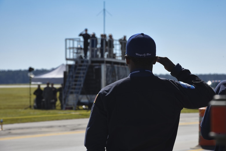 A member of the United States Air Force Academy Wings of Blue team renders a salute during the national anthem prior to the kick off of the Thunder Over South Georgia Air Show, Oct. 29, 2017, at Moody Air Force Base, Ga. Air shows aim to educate the public on past and present Air Force aerial capabilities, increase recruiting and show appreciation to the local community. (U.S. Air Force photo by Senior Airman Greg Nash)