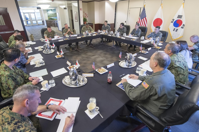 Military leaders sit around a table.