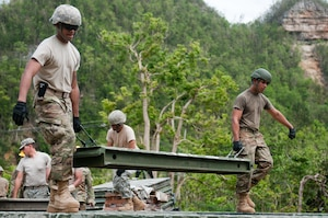 Soldiers with the 892nd Multi-Role Bridge Company, 190th Engineer Battalion from Juncos, Puerto Rico, carry a section of a 40-foot bridge they are building for the citizens of Guajataca, Puerto Rico, October 27.