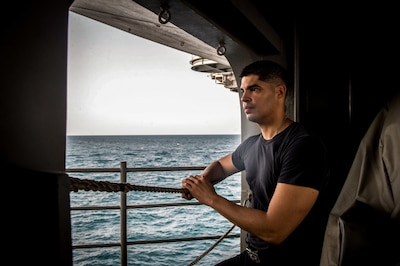 A sailor poses for a photo aboard USS Nimitz in the Persian Gulf.