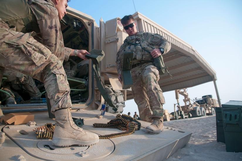 Two infantrymen prepare their vehicle.