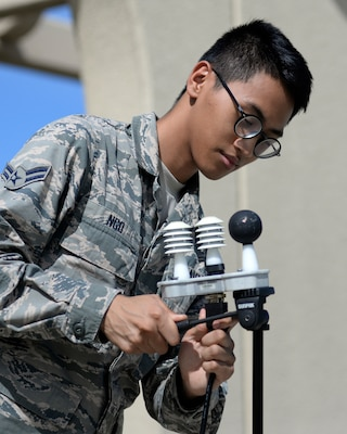 Airman sets up temperature assessment equipment.