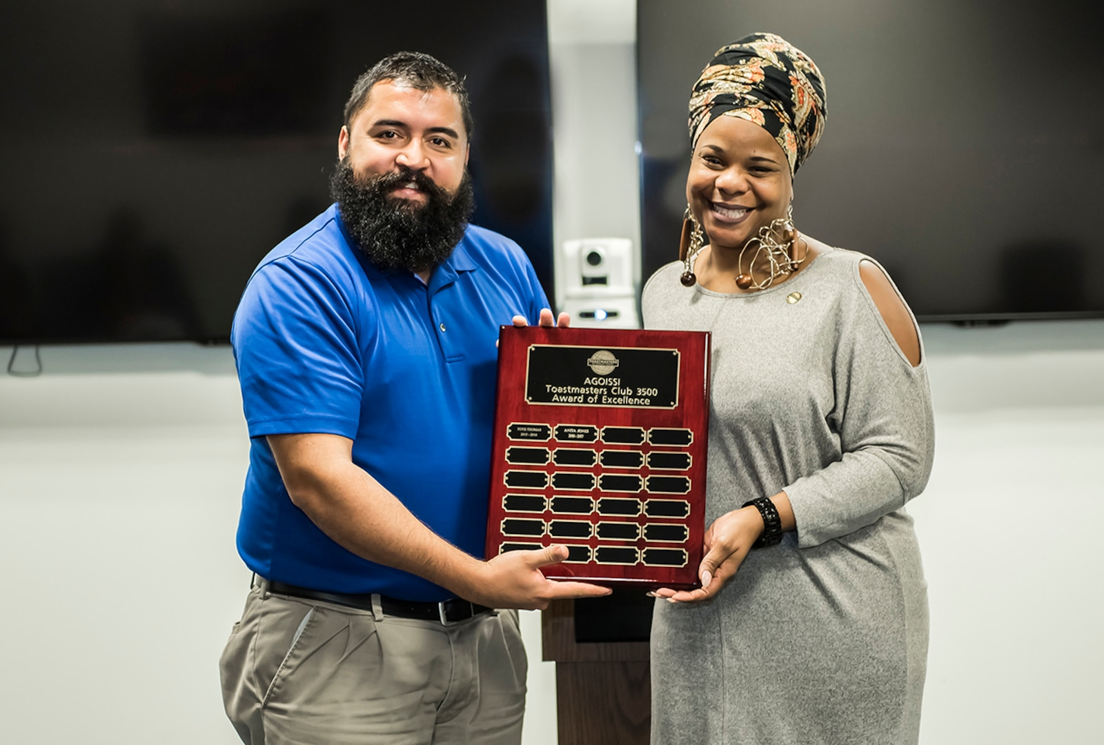 Former DLA Toastmasters AGOISSI Club President Christopher Hancock presents current Club President Anita Jones with the 2017 Frank Chi Award of Excellence.