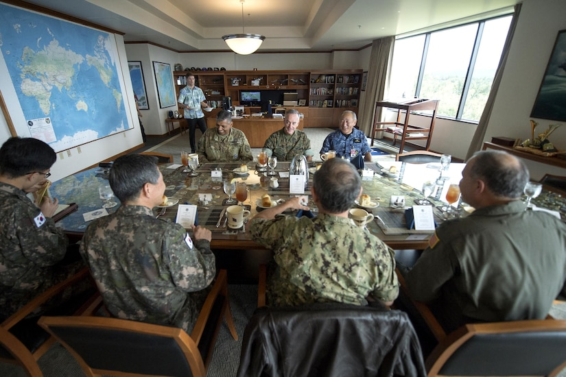 A group of senior military officials from the U.S., South Korea and Japan sit at a table.