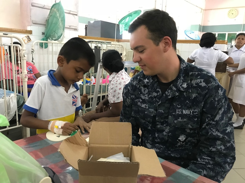 U.S. sailor helps Sri Lankan child with craft project.