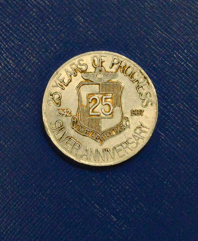A coin from Tinker's 25th Silver Anniversary. The front is a silhouette of Maj. Gen. Clarence Tinker and the back is Tinker's emblem with the years of operational service, 1942 to 1967, at the time the coin was made.