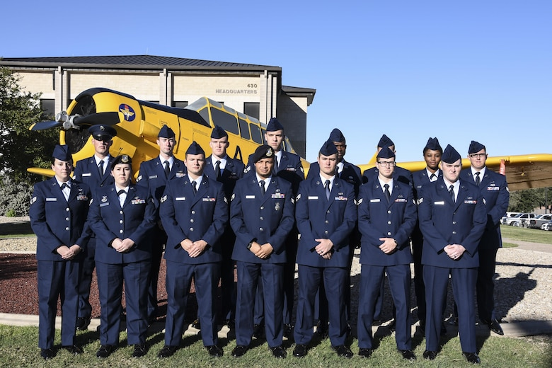 Airman Leadership School Class 17-G stands before the T-6 Texan static plane display on Goodfellow Air Force Base, Texas, Oct. 16, 2017. ALS is a six-week course designed to prepare senior airmen to assume supervisory duties by offering instruction in leadership, followership, written and oral communication skills, and the profession of arms.  (U.S. Air Force photo by Airman 1st Class Zachary Chapman/Released)