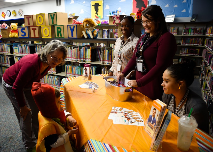 A child trick-or-treats for candy from volunteers participating in the Fall Fest at the library at Joint Base Charleston, S.C., Oct. 27, 2017.