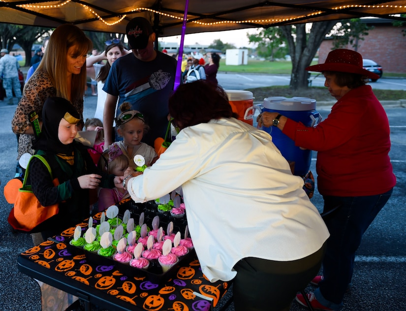 Volunteers distribute cupcakes and drinks to Fall Fest attendees outside the library at Joint Base Charleston, S.C., Oct. 27, 2017.