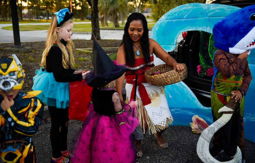 Volunteers distribute candy to families outside the library at Joint Base Charleston, S.C., Oct. 27, 2017.