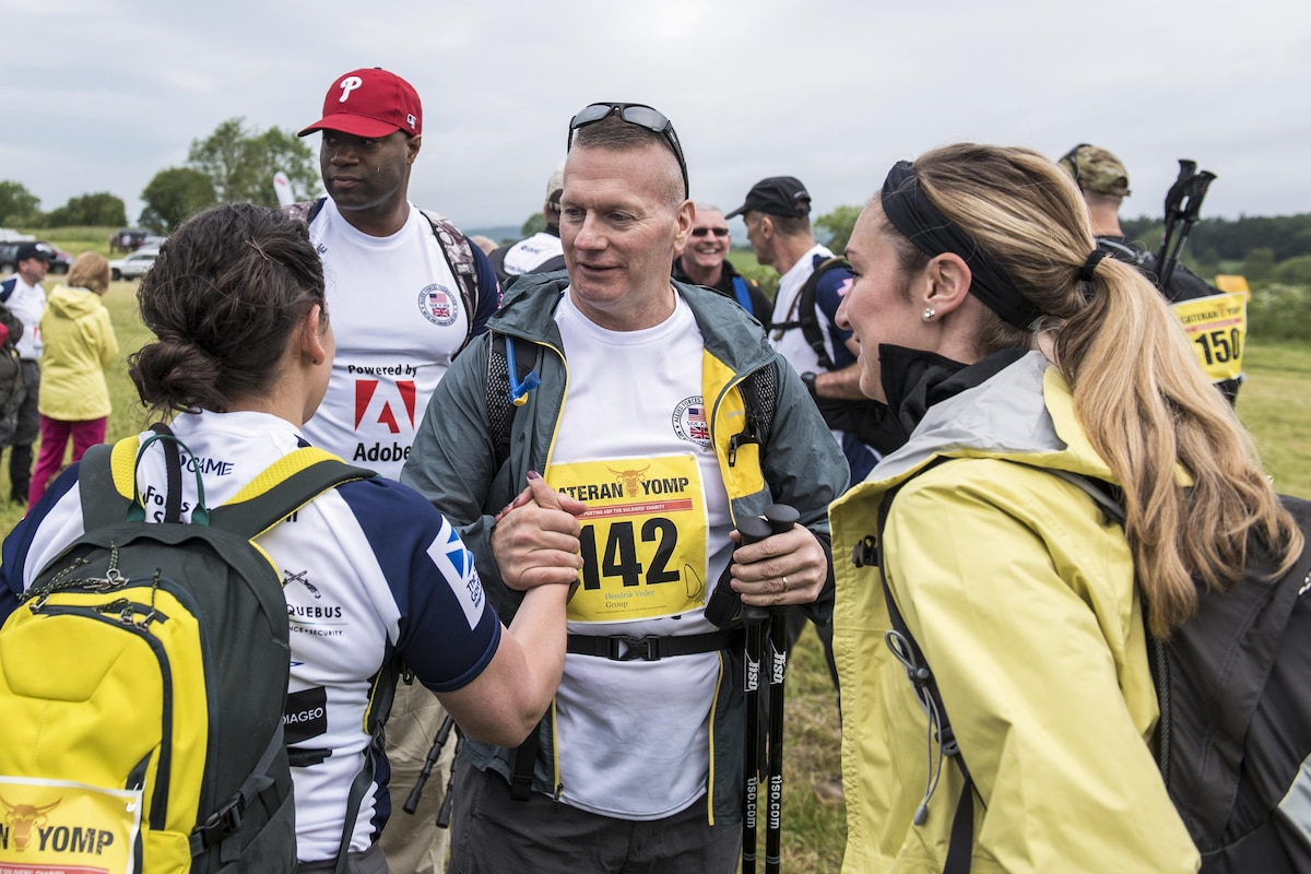The senior enlisted advisor to the chairman of the Joint Chiefs of Staff talks with participants of a hiking event.