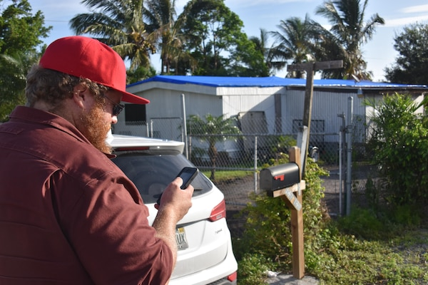 Matt Bonner, a civil engineer with the U.S. Army Corps of Engineers, Albuquerque District, and a quality assurance inspector in Florida, reviews a completed blue roof installation in Belle Grade, Florida, Oct. 23, 2017. Bonner volunteered to support Operation Blue Roof following Hurricane Irma. To date, the Corps has installed more than 11,000 temporary blue roofs for homeowners across Florida.
