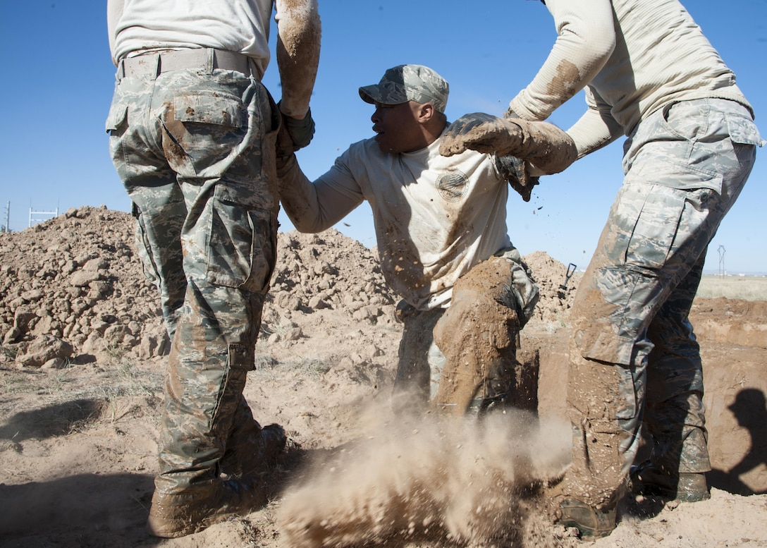 Staff Sgt. Raymond Thompkins 377th Weapons Systems Security Squadron, is assisted out of a five-foot hole by Senior Airmen Cody Ronson and Aaron Wallace, 377th WSSS, during the Manzano Challenge at Kirtland Air Force Base, N.M., Oct. 27. The competition featured Security Forces Airmen from across the 377th Security Forces Group divided into teams of four to compete on 13 stations. (U.S. Air Force photo by Staff Sgt. J.D. Strong II)