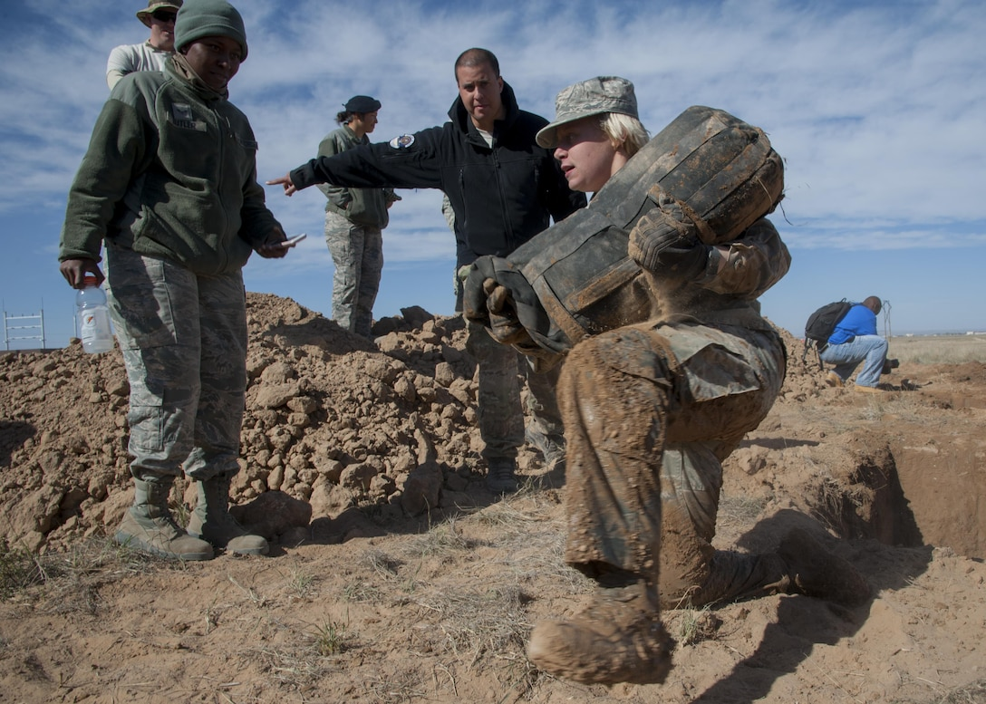 Airman 1st Class Carlie Gardner, 377th Weapons Systems Security Squadron, carries a 45-pound bag out of a five-foot hole during the Manzano Challenge at Kirtland Air Force Base, N.M., Oct. 27. The Manzano Challenge required more than 70 volunteers and coordination with 21 base agencies, making the course safe for all participants.  (U.S. Air Force photo by Staff Sgt. J.D. Strong II)