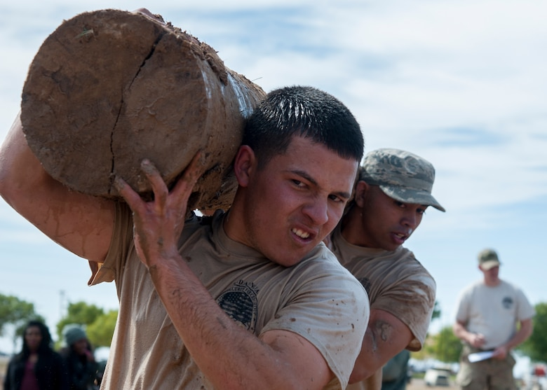 "Airman 1st Class Dalton Cruz, 377th Weapons Systems Security Squadron, carries a log with his teammate during the ""Team Punisher"" portion of the Manzano Challenge at Kirtland Air Force Base, N.M., Oct. 27. The Manzano Challenge required more than 70 volunteers and coordination with 21 base agencies, making the course safe for all participants. (U.S. Air Force photo by Staff Sgt. J.D. Strong II)"