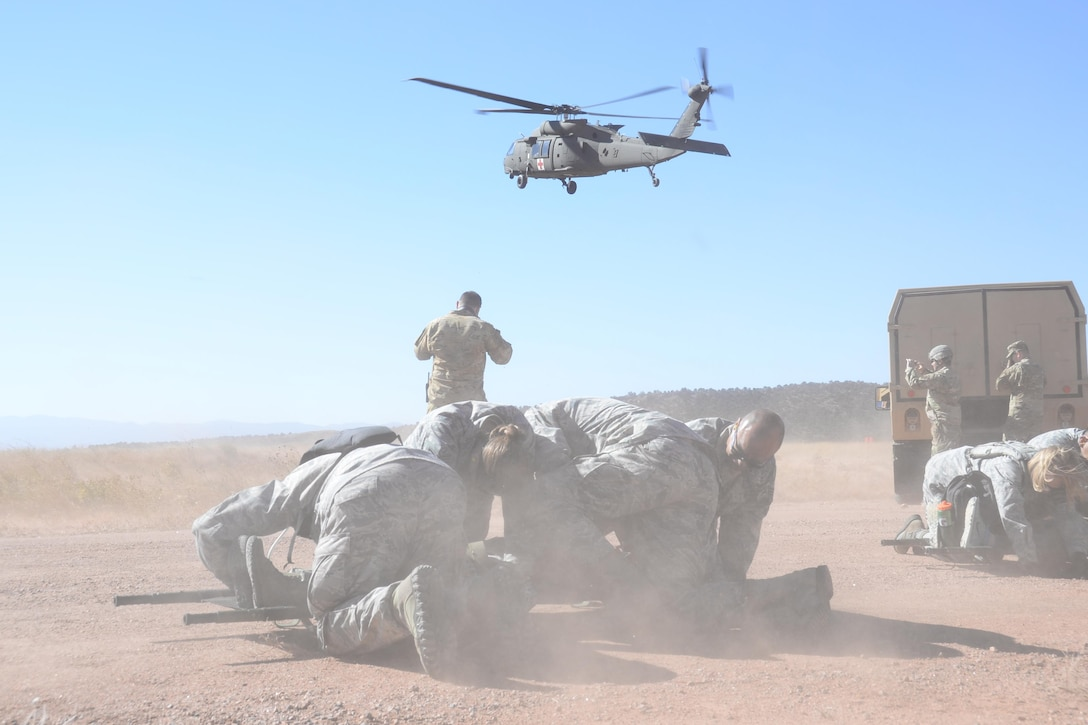Reserve Citizen Airmen with the 302nd Aeromedical Staging Squadron shield a patient strapped to a litter as a UH-60 Black Hawk helicopter kicks up dust while landing at Fort Carson's Camp Red Devil training area during a joint  exercise in Colorado Springs, Colo., Oct. 14, 2017.