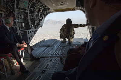 Defense Secretary Jim Mattis and a soldier look out of the tailgate of a CH-47 Chinook helicopter over Afghanistan.