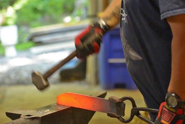 A bladesmith wields a hammer at a fiery blade.