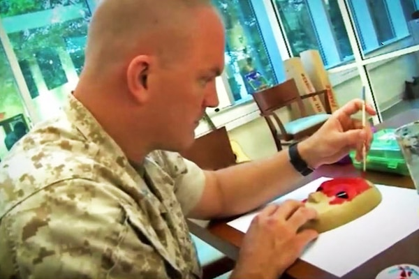 A marine paints a mask while sitting at a desk.