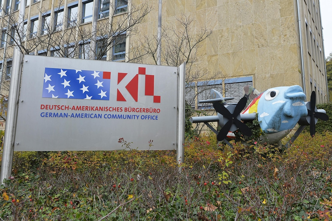 The German-American Community Office Sign stands outside the office's building next to a statue of a fish with wings at Kaiserslautern, Germany, Oct. 26, 2017. GACO serves as a link between the German and American populations in the Kaiserslautern Military Community. (U.S. Air Force photo by Airman 1st Class Joshua Magbanua)