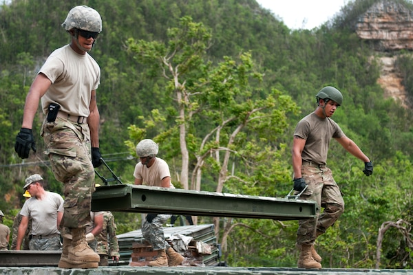Puerto Rico Army National Guardsmen carry a section of a 40-foot bridge they are building for the citizens of Quebradillas, Puerto Rico, Oct. 27, 2017. Army photo by Sgt. Michael Eaddy