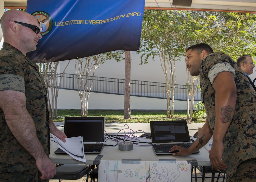 """U.S. Marine Corps SSgt Michael George, USCENTCOM cybersecurity technician (Left), and U.S. Marine Corps SSgt. William Berotte, USCENTCOM cybersecurity technician (Right), demonstrate how simple it is to """"hack"""" on older computer operating system at the USCENTCOM cybersecurity awareness expo, October 26, 2017. The expo provided the opportunity for personnel and family members to talk with subject matter experts and view exhibits that highlight best security practices, in the workplace and home, to protect critical and personal information online."""