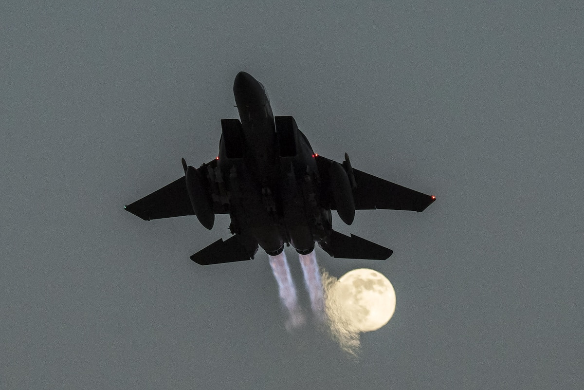 An aircraft takes off with a full moon in the sky.