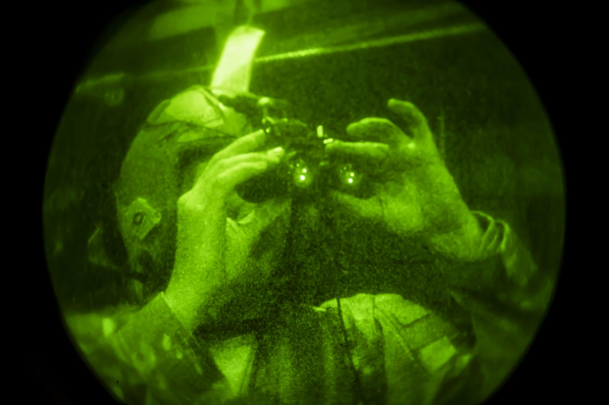 Airman looks through night vision goggles.
