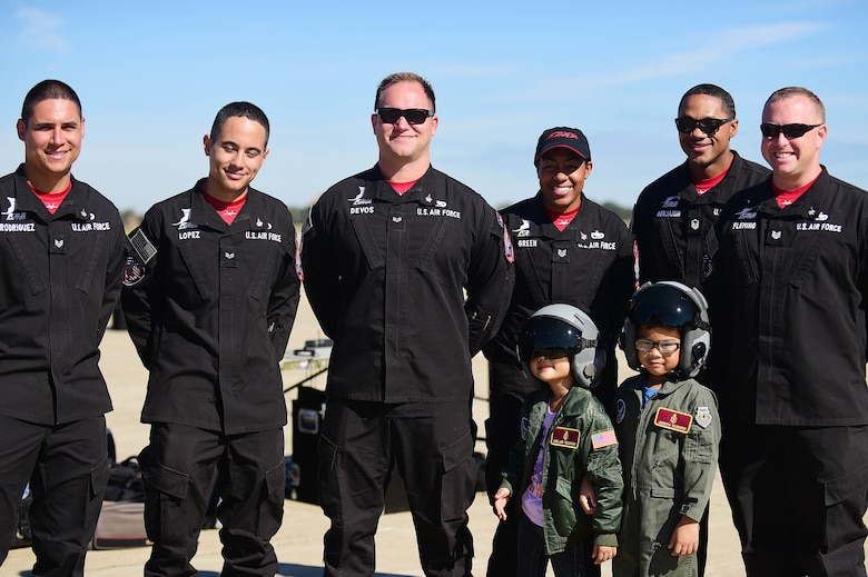 F-22 Raptor Demonstration Team members posing for a photo with two children dressed in flight suits.