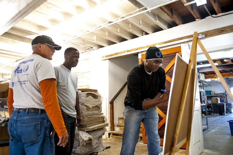 U.S. Air Force Staff Sgt. Adam Baty, 17th Communications Squadron client systems technician, Staff Sgt. Louis Perry, 17th CS client systems technician, and a Habitat for Humanity volunteer, go over plans for their volunteer day for HFH center in San Angelo, Texas, Oct. 26, 2017. 17th CS spent most of the day reorganizing and preparing HFH for a fundraising event. (U.S. Air Force photo by Senior Airman Scott Jackson/Released)