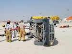 Air Force firefighters in Qatar practice their extrication skills using a vehicle obtained from DLA Disposition Services.