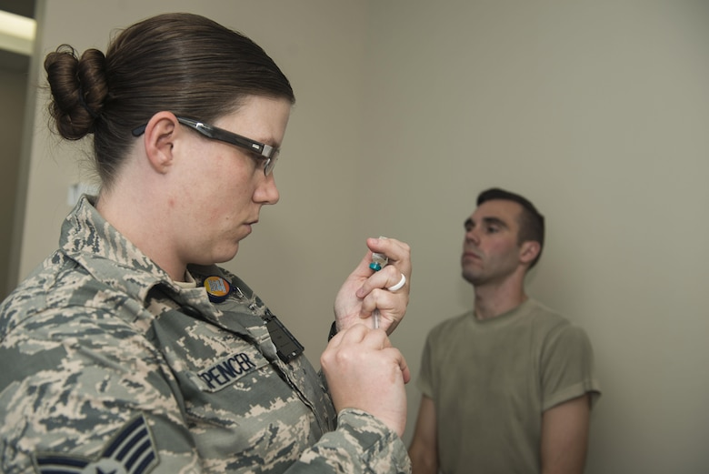 U.S. Air Force Staff Sgt. Jake Spencer, 20th Medical Operations Squadron immunizations backup technician, prepares a vaccine for Capt. Adam Gadson, 20th Logistics Readiness Squadron operations officer, at Shaw Air Force Base, South Carolina, Oct. 23, 2017.