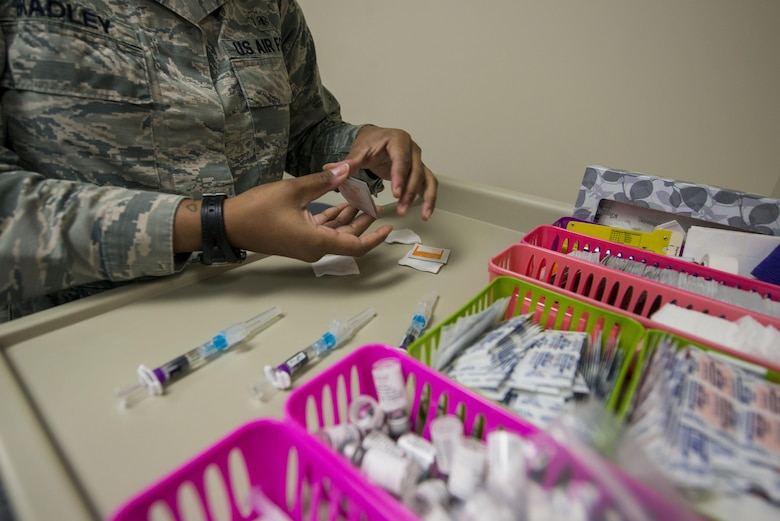 U.S. Air Force Senior Airman Tamika Bradley, 20th Medical Operations Squadron allergy and immunizations technician, opens packets of wipes prior to administering a vaccine at Shaw Air Force Base, South Carolina, Oct. 23, 2017.