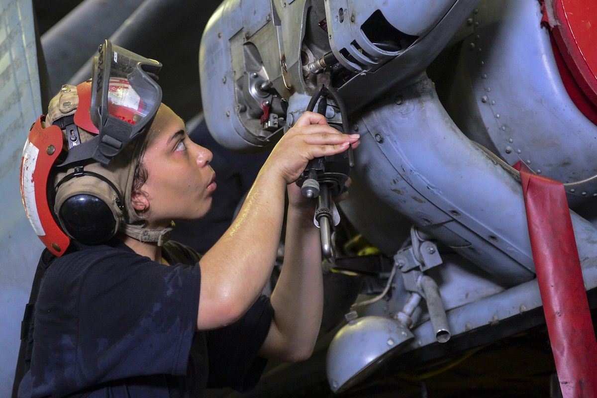 A sailor maintains a crane for a Seahawk helicopter.