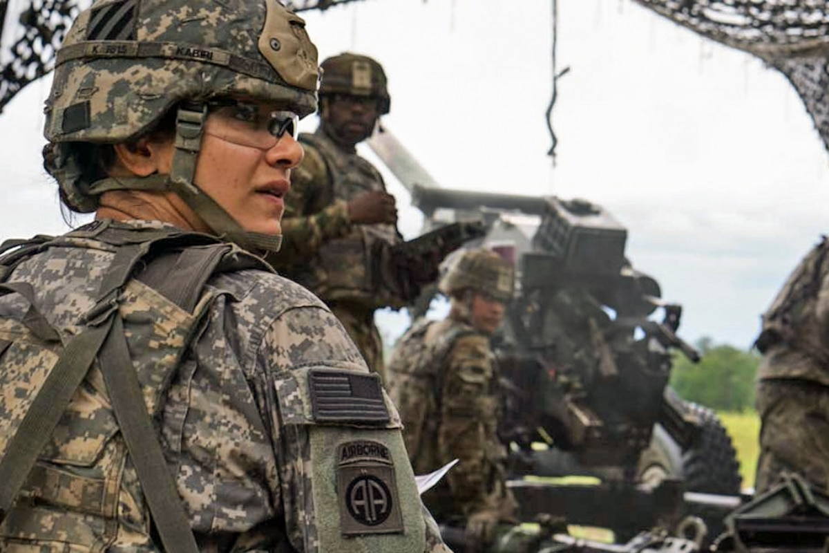 An Army captain helps her team prepare a howitzer.