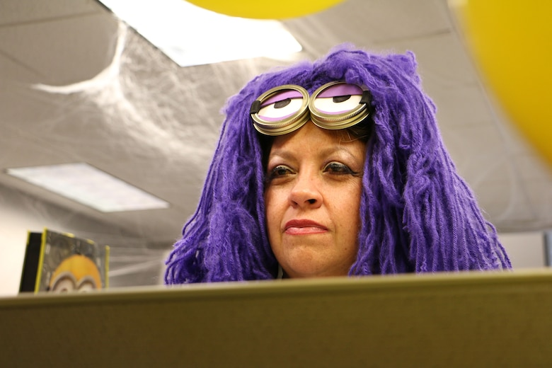 "Gina Garcia, 21st Contracting Squadron contracting specialist, peers over her cubicle while dressed as a purple minion from the movie series ""Despicable Me"" at Peterson Air Force Base, Colorado, Oct. 31, 2017. Some units on Peterson AFB dressed in costume to celebrate Halloween. (U.S. Air Force photo by Staff Sgt. Erica Picariello)"