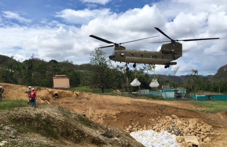 A Chinook helicopter from the Georgia National Guard places 3,000-pound supersacks in the damaged spillway. Altogether, 505 jersey barriers and 1,300 supersacks will be placed to minimize further erosion in the damaged spillway.