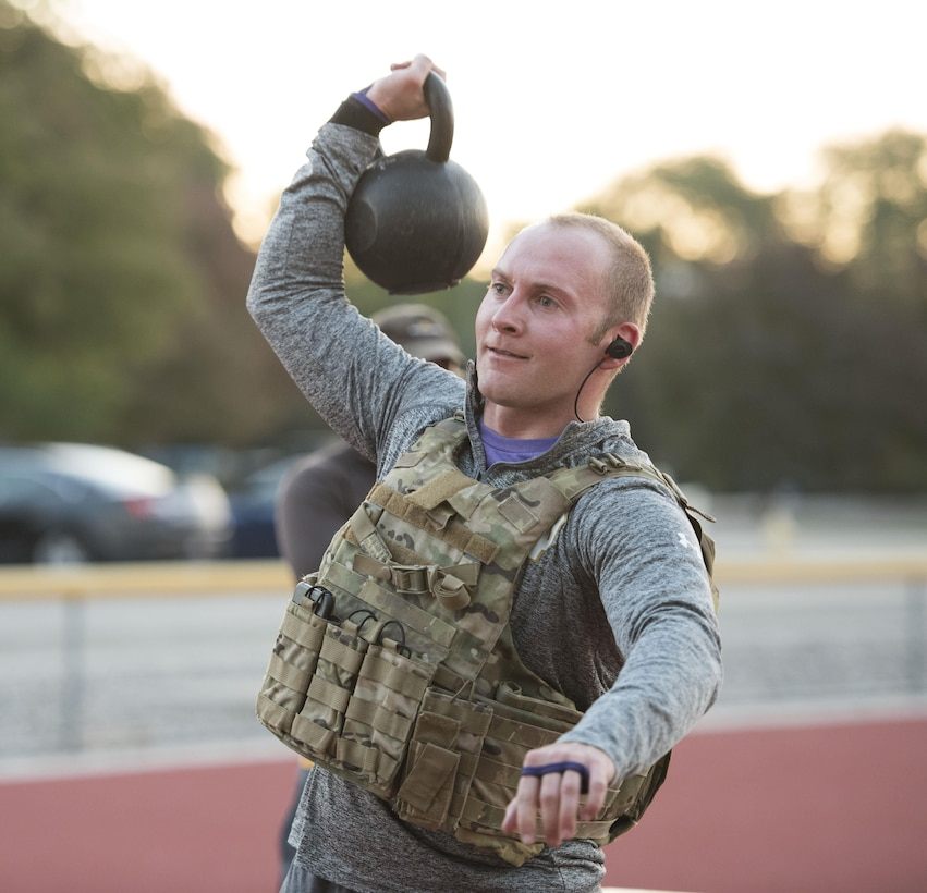 An Airman from the 366th Civil Engineer explosive ordnance disposal unit lifts a kettlebell at the EOD memorial workout Sept. 29, 2017, at Mountain Home Air Force Base, Idaho. The workout involved weighted front squats, kettle bell swings, barbell rows, chest-to-bar pull-ups and a run. (U.S. Air Force photo by Airman 1st Class Alaysia Berry)