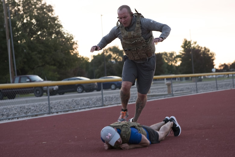 An Airman from the 366th Civil Engineer explosive ordnance disposal unit jumps over his partner and launches into a burpee at the EOD memorial workout Sept. 29, 2017, at Mountain Home Air Force Base, Idaho. The workout was performed in remembrance of all the EOD technicians who lost their lives after Sept. 11, 2001. (U.S. Air Force photo by Airman 1st Class Alaysia Berry)