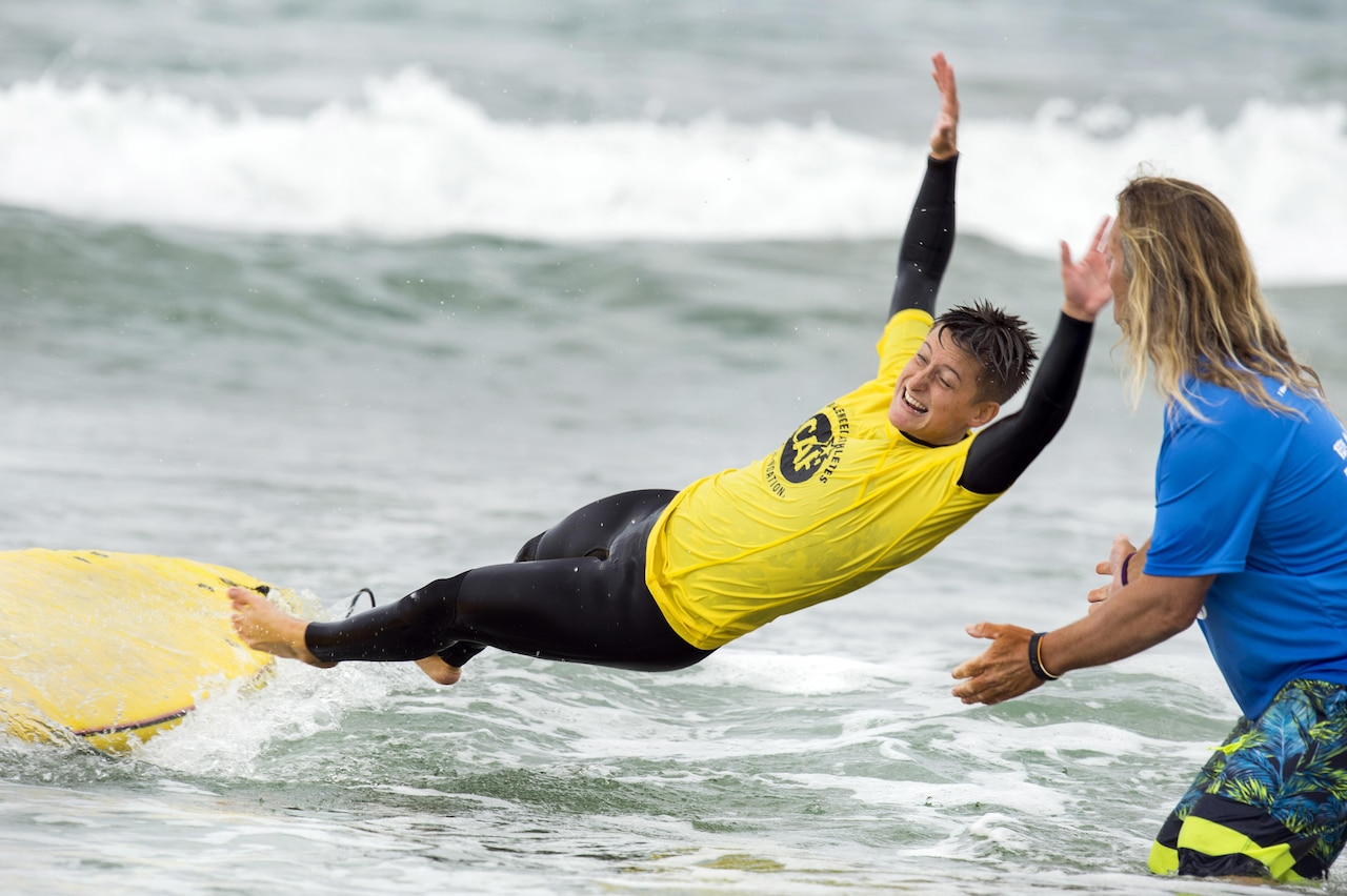 A surfer free falls from a surfboard and next to an instructor.