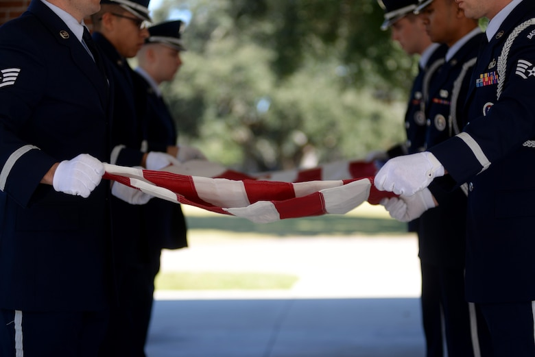 Keesler Air Force Base Honor Guard members practice flag folding procedures before a funeral ceremony Oct. 26, 2017, at the Biloxi National Cemetery in Biloxi, Mississippi. Before every funeral detail, honor guardsmen arrive an hour early to practice their roles to ensure each move is precise. (U.S. Air Force photo by Airman 1st Class Suzanna Plotnikov)